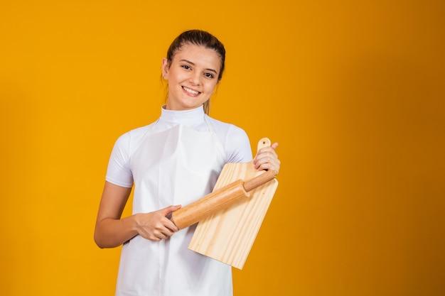 Jonge blanke vrouw met schort, vleesplank en deegroller op gele achtergrond. koken