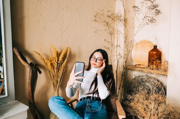 Jonge blanke vrouw met smartphone die op cel kijkt met behulp van mobiele telefoontechnologie thuis