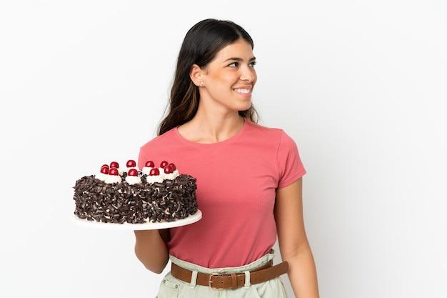 Jonge blanke vrouw met verjaardagstaart geïsoleerd op een witte achtergrond op zoek naar de kant