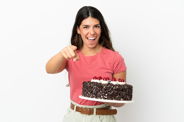 Jonge blanke vrouw met verjaardagstaart geïsoleerd op een witte achtergrond verrast en wijzend naar voren