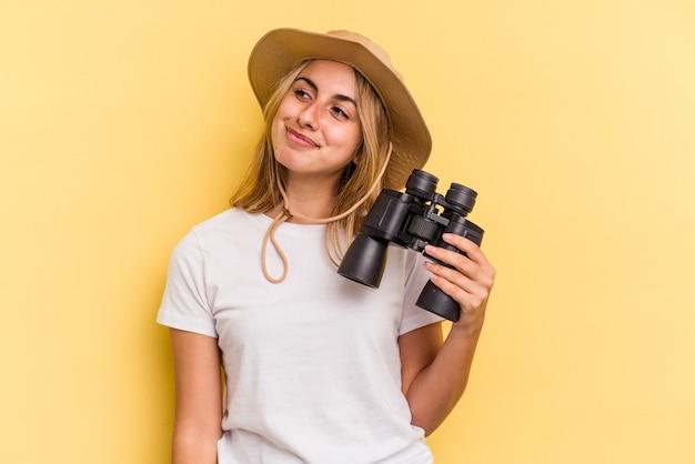 Jonge blanke vrouw met verrekijker geïsoleerd op gele achtergrond dromen van het bereiken van doelen en doeleinden
