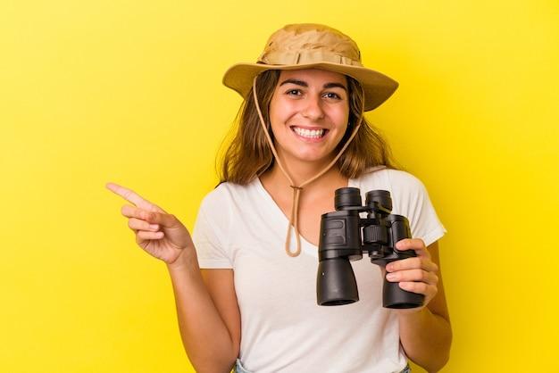 Jonge blanke vrouw met verrekijker geïsoleerd op gele achtergrond glimlachend en opzij wijzend, iets tonend op lege ruimte.