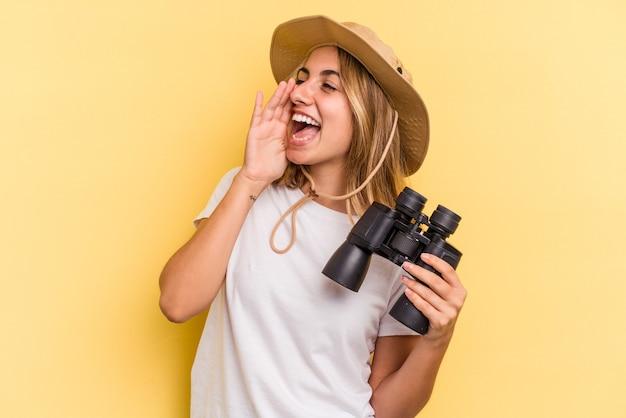 Jonge blanke vrouw met verrekijker geïsoleerd op gele achtergrond schreeuwen en houden palm in de buurt van geopende mond.