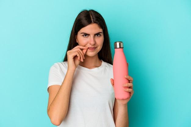 Jonge blanke vrouw met waterfles geïsoleerd op blauwe achtergrond met vingers op lippen die een geheim houden.