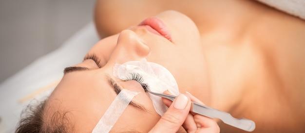 Jonge blanke vrouw met wimper extensie procedure in de schoonheidssalon. schoonheidsspecialiste lijmt wimpers met een pincet