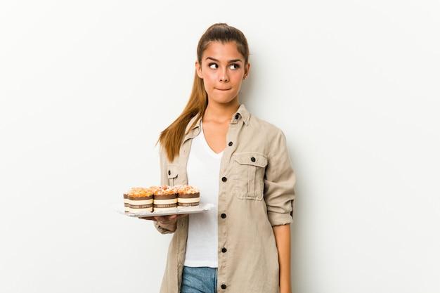 Jonge blanke vrouw met zoete cakes verward, voelt zich twijfelachtig en onzeker.