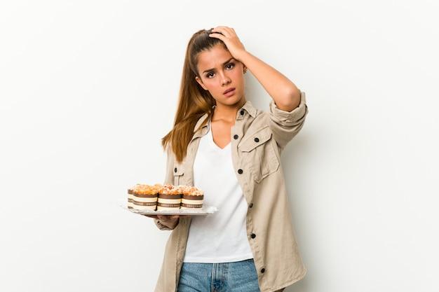 Jonge blanke vrouw met zoete cakes wordt geschokt, ze heeft belangrijke vergadering onthouden.