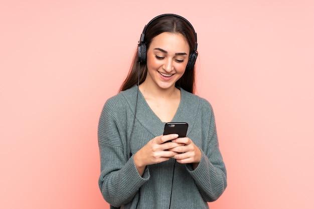 Jonge blanke vrouw muziek luisteren en op zoek naar mobiel
