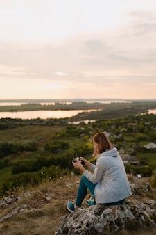 Jonge blanke vrouw navigeren een vliegende drone met afstandsbediening