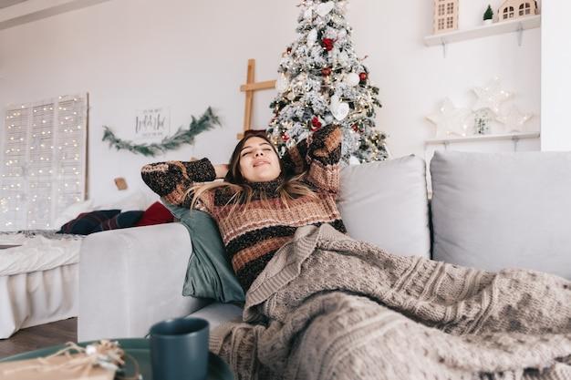 Jonge blanke vrouw ontspannen op een bank thuis in kerstvakantie.
