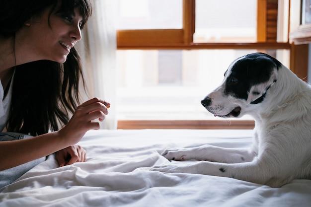 Jonge blanke vrouw op bed met haar schattige puppy hond spelen en geven hem traktaties. liefde voor dieren concept. levensstijl binnenshuis