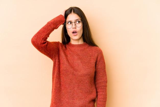 Jonge blanke vrouw op beige muur wordt geschokt, ze heeft belangrijke bijeenkomst herinnerd.