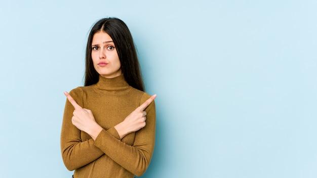 Jonge blanke vrouw op blauwe muur wijst zijwaarts, probeert te kiezen tussen twee opties.