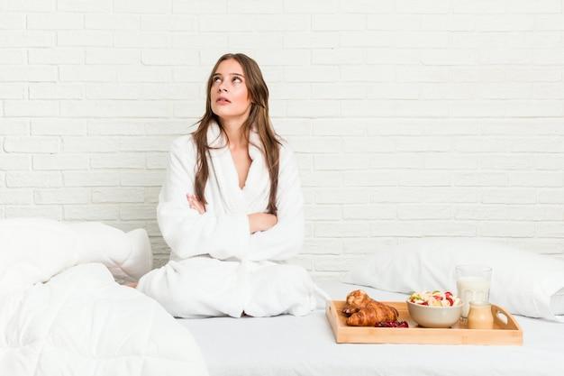 Jonge blanke vrouw op het bed moe van een repetitieve taak