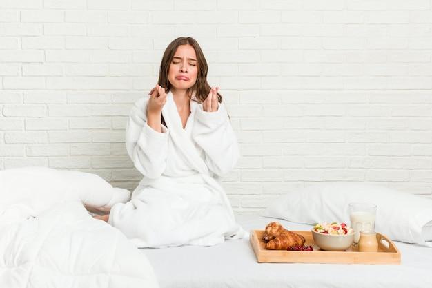 Jonge blanke vrouw op het bed waaruit blijkt dat ze geen geld heeft.