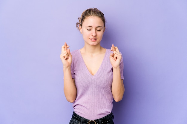 Jonge blanke vrouw op paarse kruising vingers voor het hebben van geluk