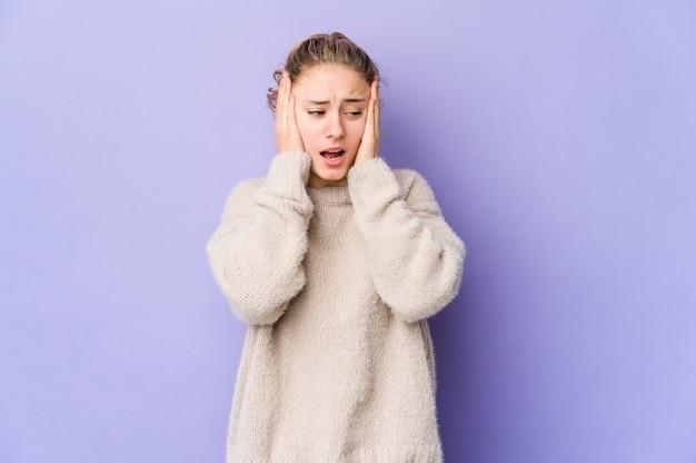Jonge blanke vrouw op paarse muur die oren bedekt met handen die proberen niet te hard geluid te horen.