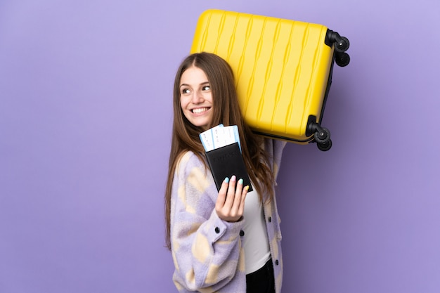 Jonge blanke vrouw op paarse muur in vakantie met koffer en paspoort