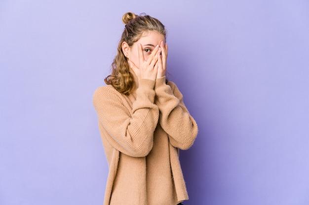 Jonge blanke vrouw op paarse muur knipperen door angstige en nerveuze vingers.