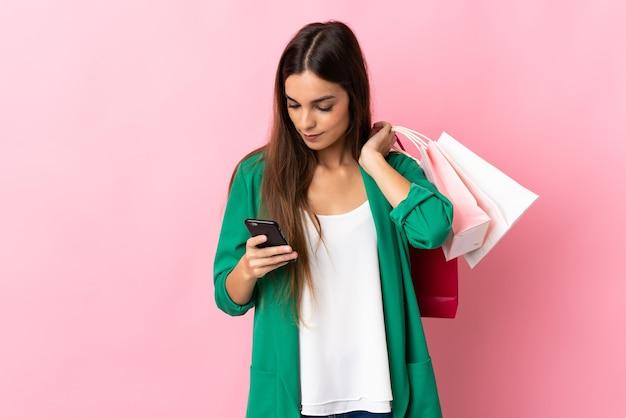 Jonge blanke vrouw op roze boodschappentassen te houden en een bericht te schrijven met haar mobiele telefoon naar een vriend
