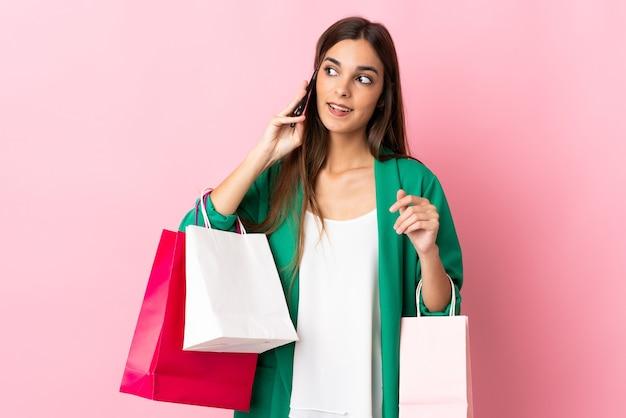 Jonge blanke vrouw op roze boodschappentassen te houden en een vriend te bellen met haar mobiele telefoon