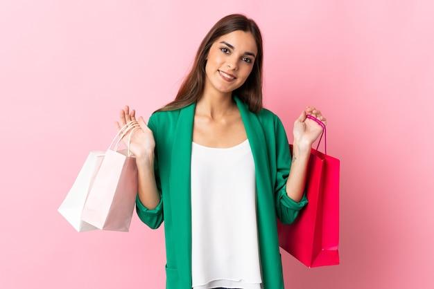 Jonge blanke vrouw op roze boodschappentassen te houden en glimlachen