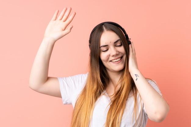 Jonge blanke vrouw op roze muur luisteren muziek en dansen