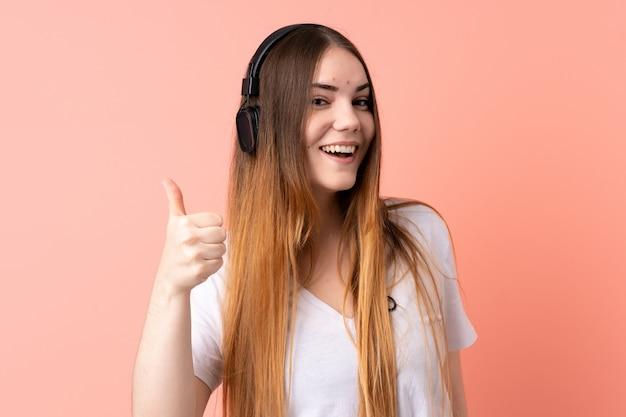 Jonge blanke vrouw op roze muur luisteren muziek en met duim omhoog