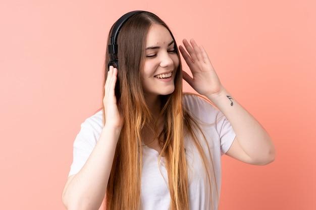 Jonge blanke vrouw op roze muur luisteren muziek en zingen