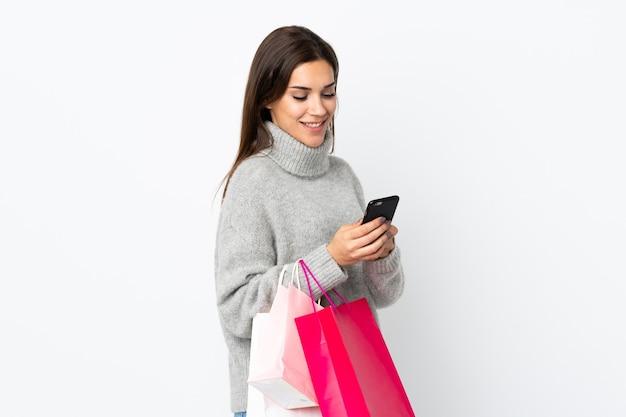 Jonge blanke vrouw op wit met boodschappentassen en een bericht schrijven met haar mobiele telefoon naar een vriend