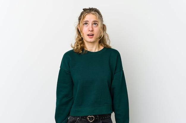 Jonge blanke vrouw op witte achtergrond schreeuwen erg boos, gefrustreerd woedeconcept.