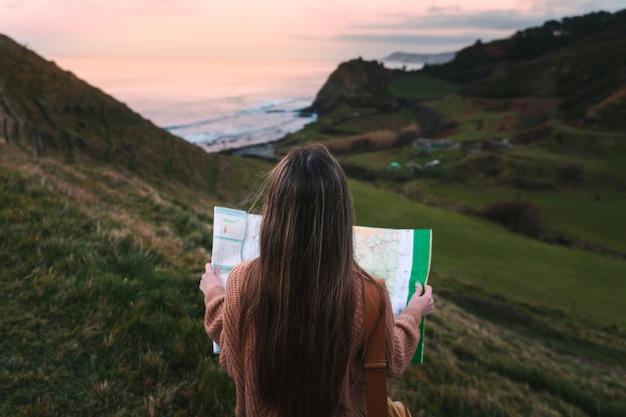 Jonge blanke vrouw op zoek naar een kaart op een natuurpark naast de kust