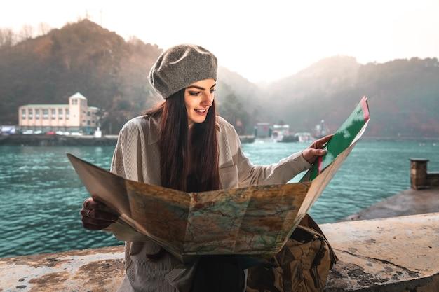 Jonge blanke vrouw op zoek naar een kaart tijdens een bezoek aan een stad aan zee.