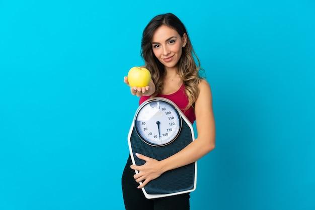 Jonge blanke vrouw over de geïsoleerde weegmachine van de muurholding en het aanbieden van een appel