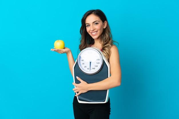 Jonge blanke vrouw over geïsoleerde achtergrond met weegmachine en met een appel