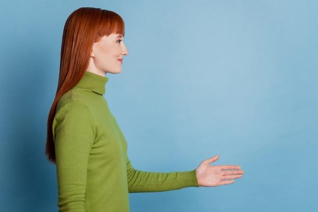 Jonge blanke vrouw over geïsoleerde blauwe achtergrond handen schudden