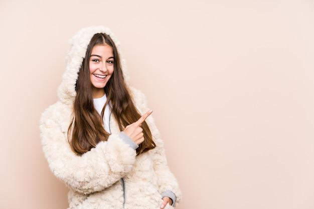 Jonge blanke vrouw poseren geïsoleerd glimlachend en opzij wijzend, iets op lege ruimte tonen.