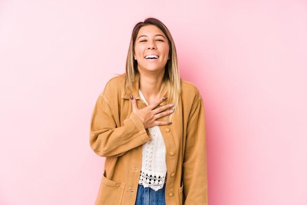 Jonge blanke vrouw poseren geïsoleerd lacht luid houden hand op de borst.