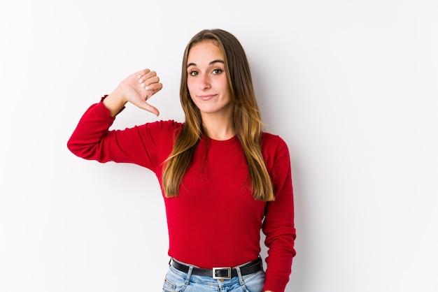 Jonge blanke vrouw poseren geïsoleerd met een afkeer gebaar, duimen naar beneden. meningsverschil concept.