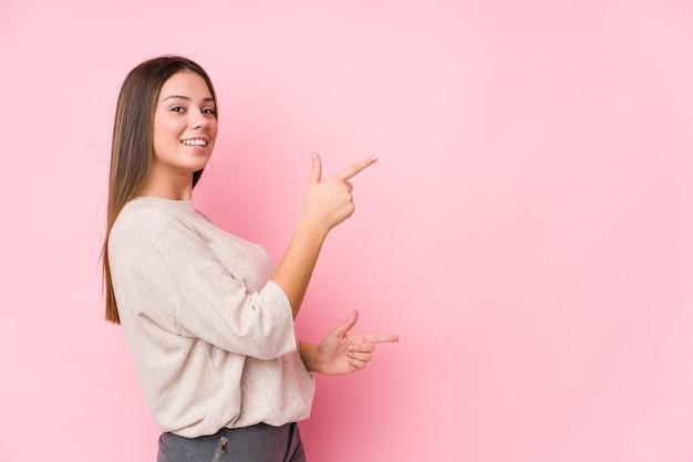 Jonge blanke vrouw poseren geïsoleerd opgewonden wijzend met wijsvingers weg.