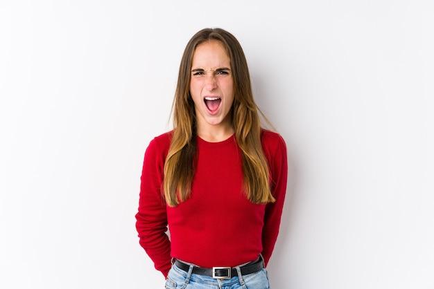Jonge blanke vrouw poseren geïsoleerd schreeuwen erg boos en agressief.