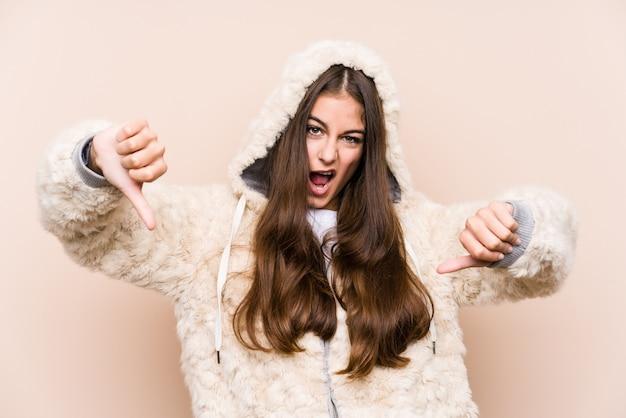 Jonge blanke vrouw poseren geïsoleerd tonen duim omlaag en afkeer uiten