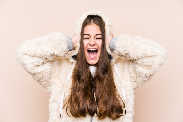 Jonge blanke vrouw poseren geïsoleerd voor oren met handen proberen niet te hard geluid te horen.
