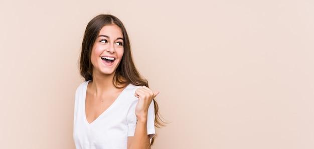 Jonge blanke vrouw poseren punten met duim vinger weg, lachen en zorgeloos.