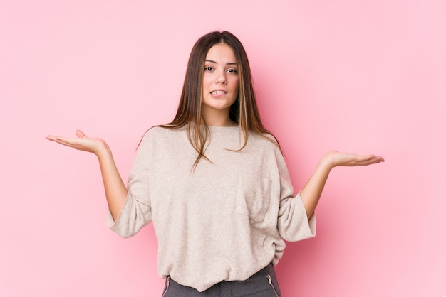 Jonge blanke vrouw poseren verward en twijfelachtig schouders ophalen om een lege ruimte te houden.