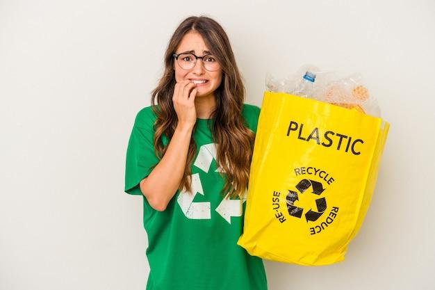 Jonge blanke vrouw recycling een vol plastic geïsoleerd op een witte achtergrond vingernagels bijten, nerveus en erg angstig.