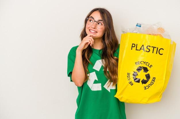 Jonge blanke vrouw recycling een vol plastic geïsoleerd op een witte achtergrond zijwaarts kijkend met twijfelachtige en sceptische uitdrukking.