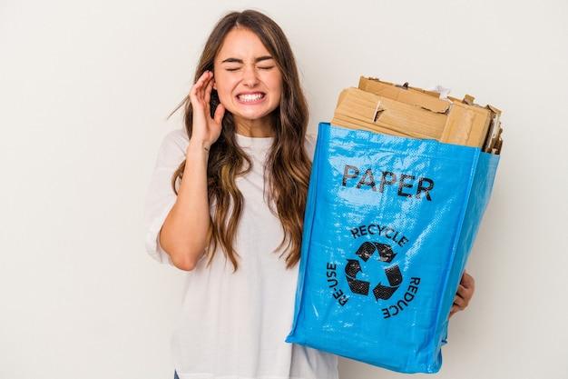Jonge blanke vrouw recycling papier geïsoleerd op een witte achtergrond die betrekking hebben op oren met handen.