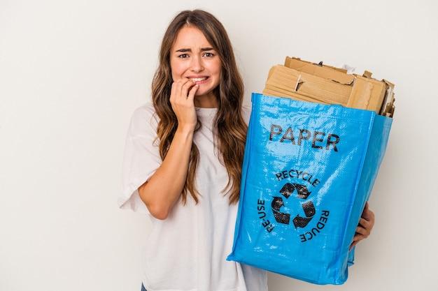Jonge blanke vrouw recycling papier geïsoleerd op een witte achtergrond vingernagels bijten, nerveus en erg angstig.