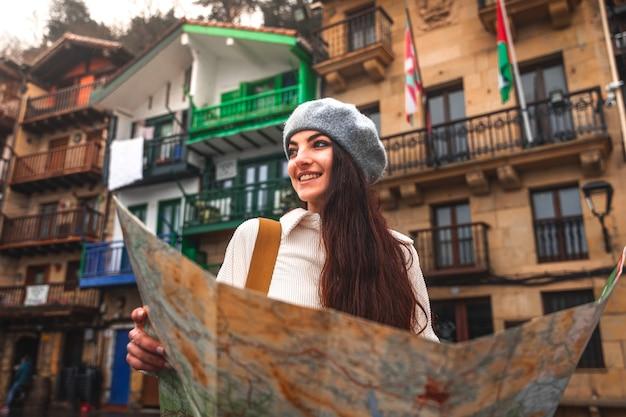 Jonge blanke vrouw reiziger op zoek naar een kaart en kleurrijke gevels achter
